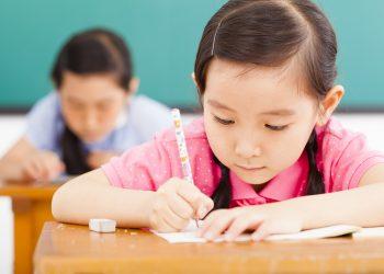 children in classroom with pen in hand