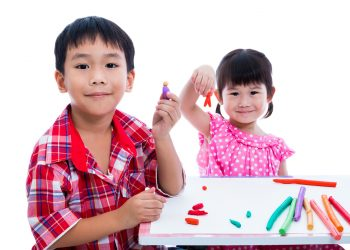 Little asian children playing and creating toys from play dough on table. Boy and girl smiling and show works from clay at camera, over white background. Strengthen the imagination of child